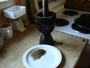 Cumin being ground in a mortar and pestle.