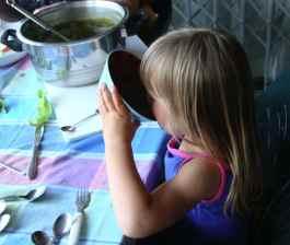 A small child, Beth, enjoying broccoli soup.